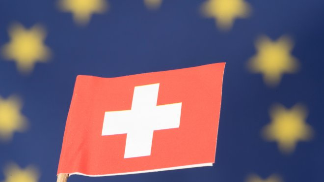 Swiss Flag, in the Background a large EU Flag