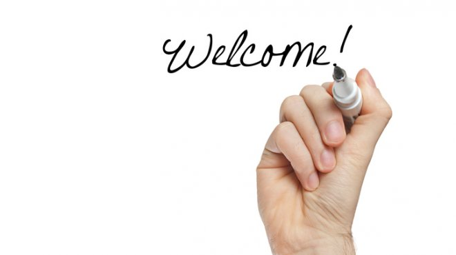 "Une main écrit ""welcome!"""